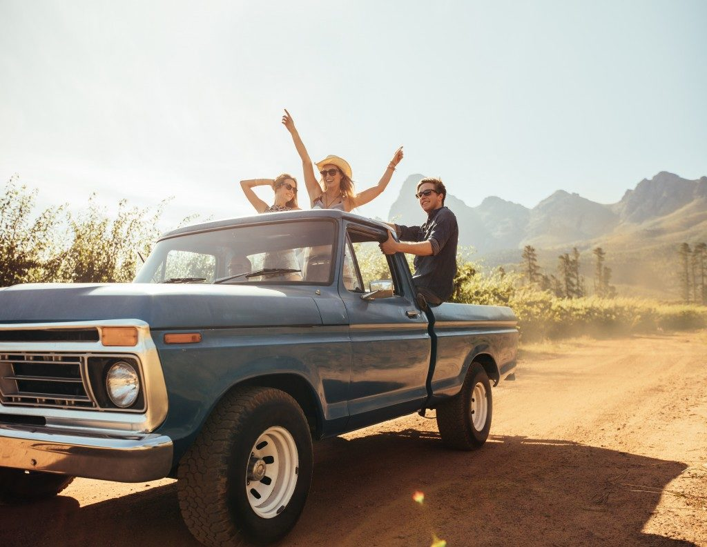 Group of people at the back of a pick up truck having fun