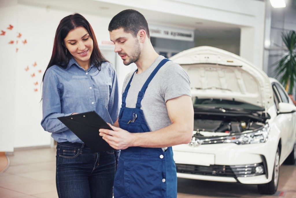 Car mechanic with a customer