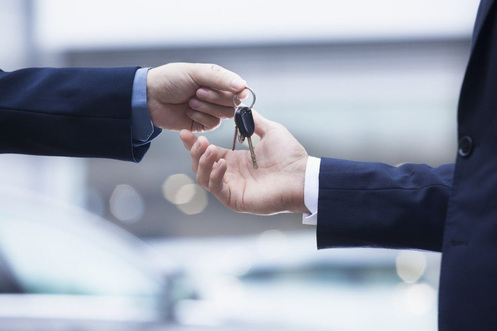 Man handing over keys to new car
