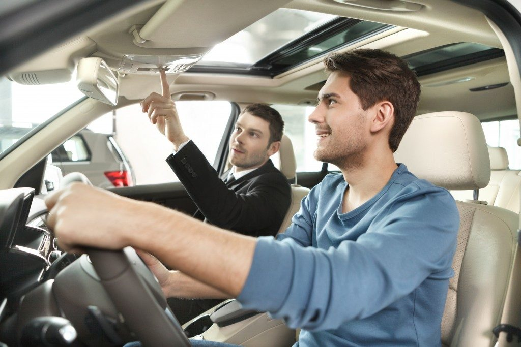 car salesman showing features of the car to customer