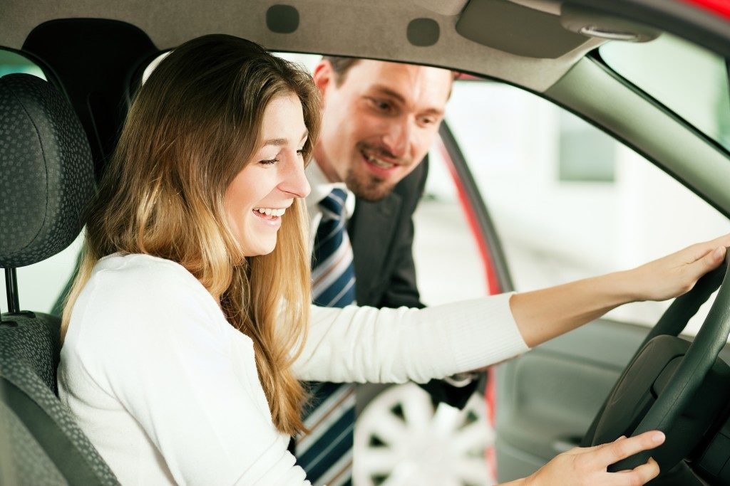 woman looking at the car with salesman