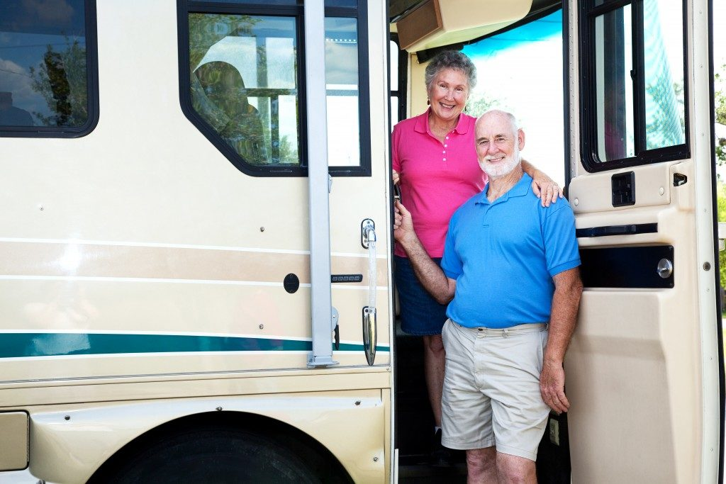 old couple standing inside their RV