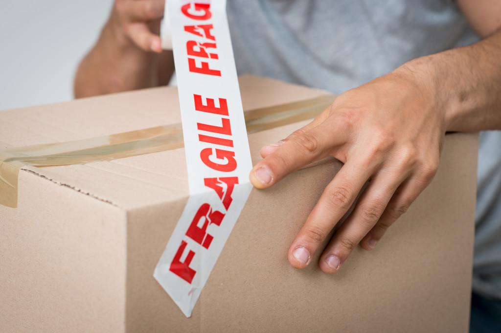 man adhering sticker to a box